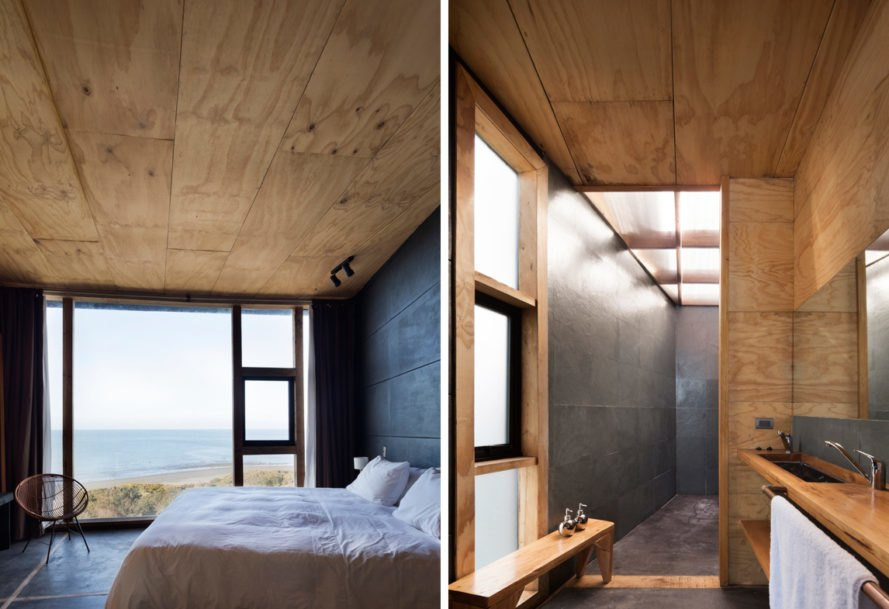 On the left, white bed near large window overlooking the sea. On the right, light wood bathroom.
