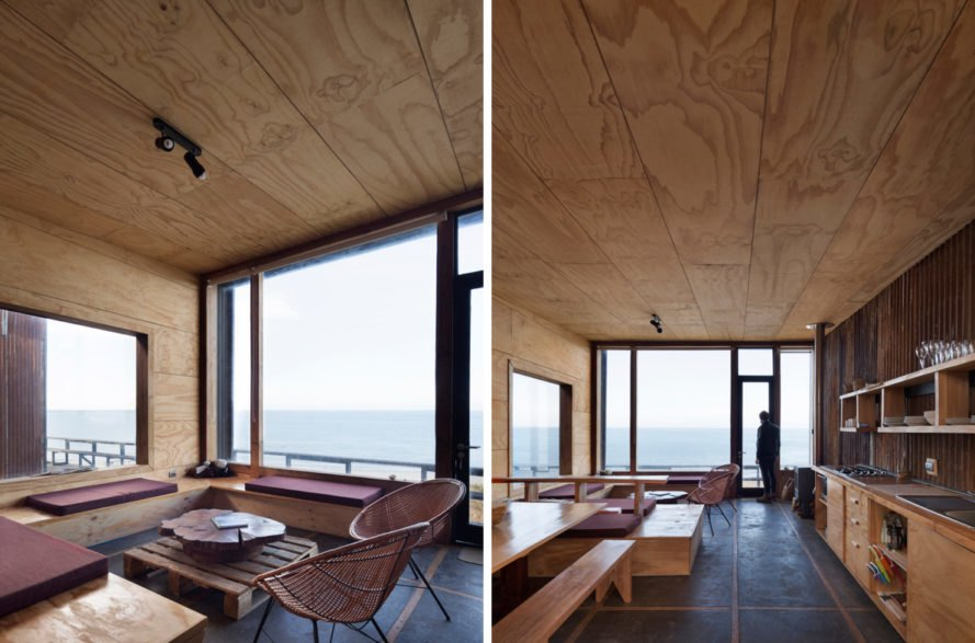 On the left, cushioned benches near window overlooking the sea. On the right, wood benches and wood kitchen cabinets.