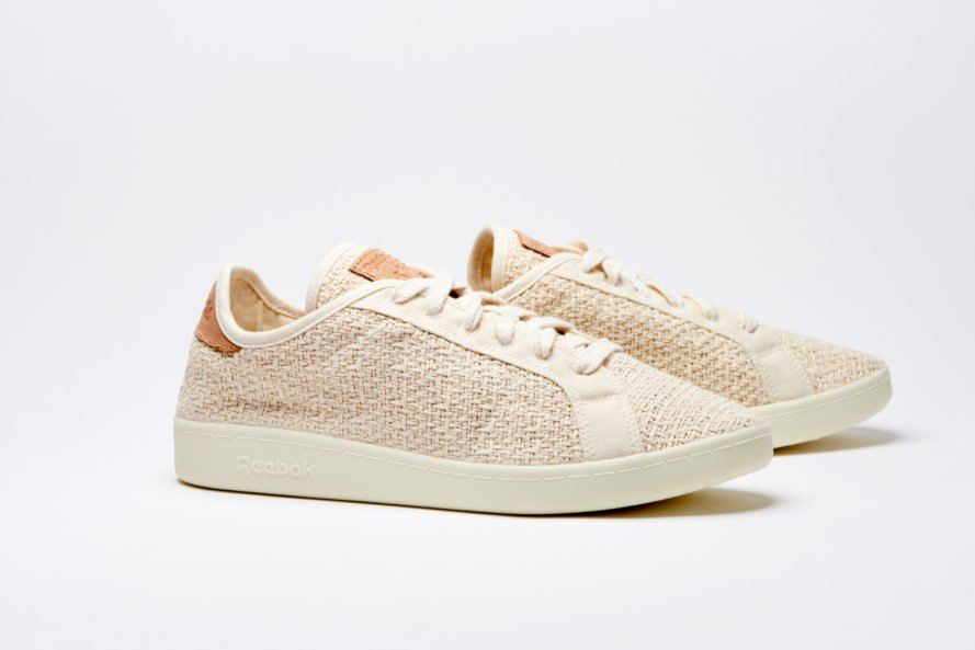 Angled side view of light tan Reebok sneakers