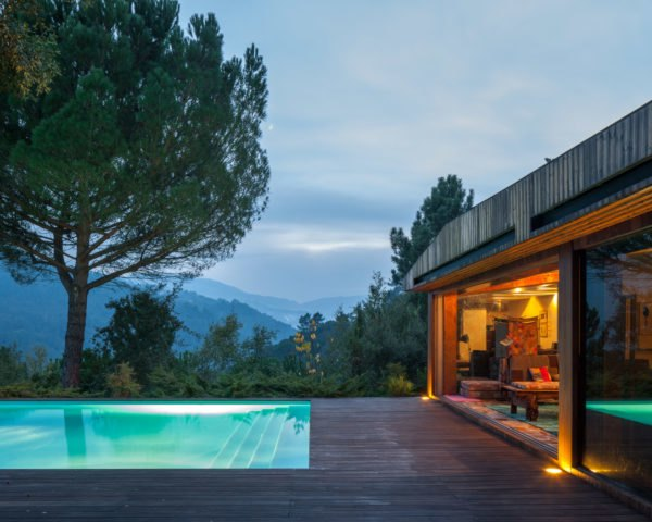 Home with glass walls at dusk and pool
