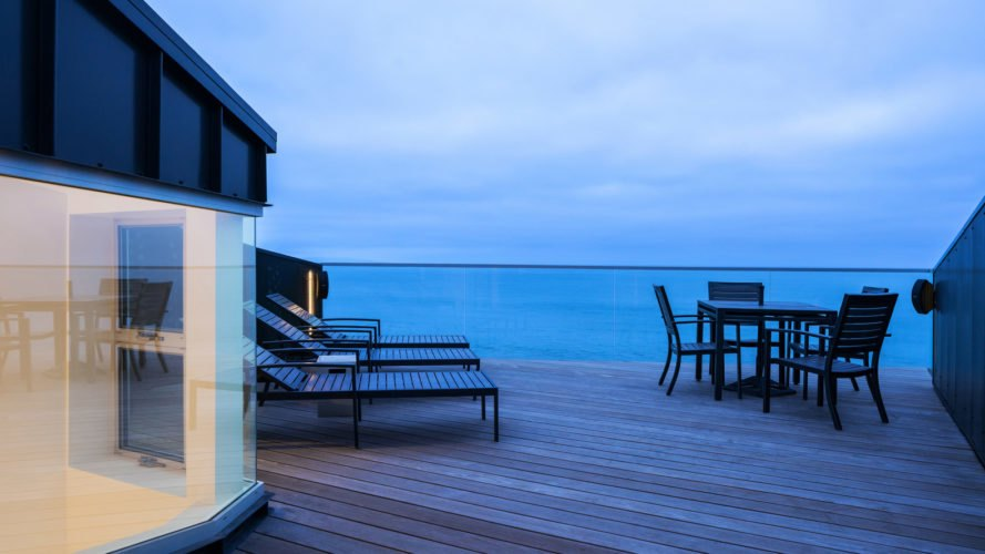 outdoor deck with views of beach and lounge chairs at dusk