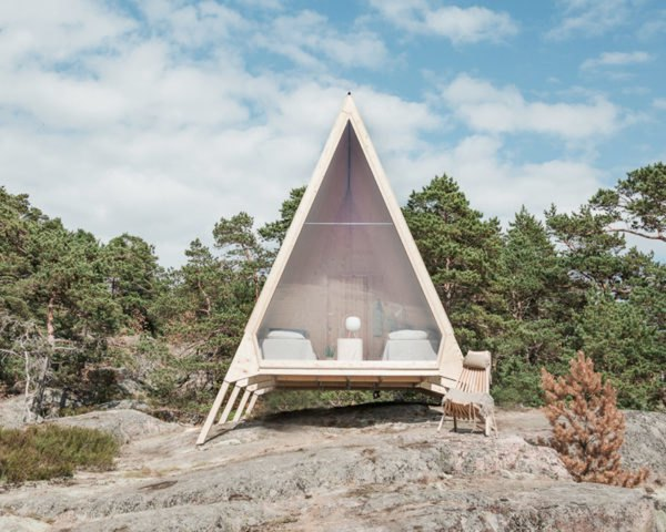 A-frame timber cabin with glass wall revealing beds inside