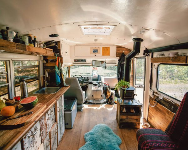 interior of a school bus converted into a cozy tiny house