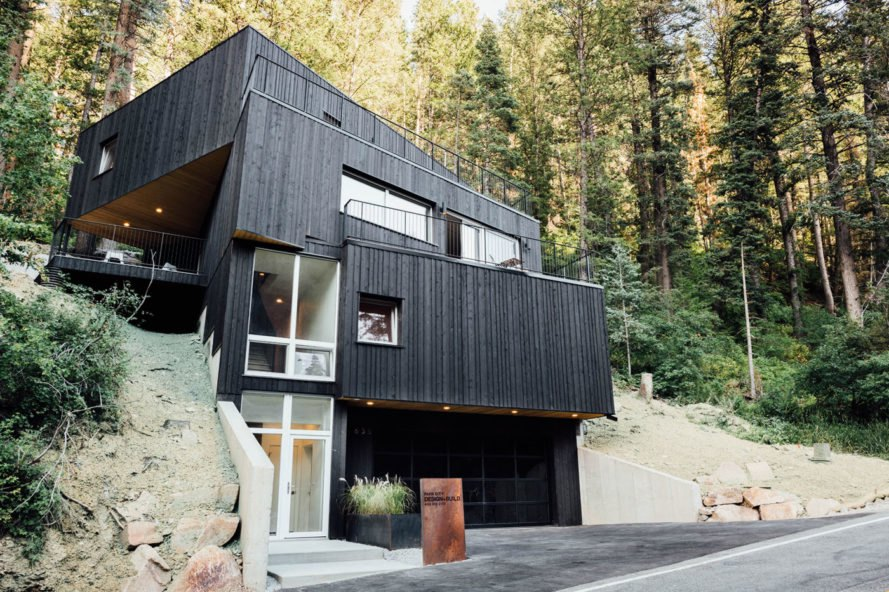 boxy black house with pine forest in background