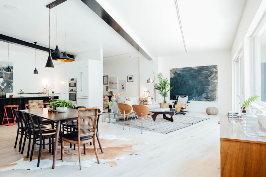 open plan living and dining area with white walls and floor