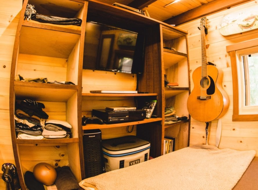 wall of shelving with guitar hanging on the guitar