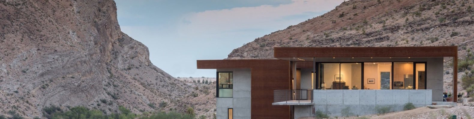 concrete and weathered steel home in a desert landscape