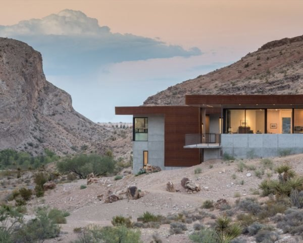 concrete and weathered steel home in a desert landscape at dusk