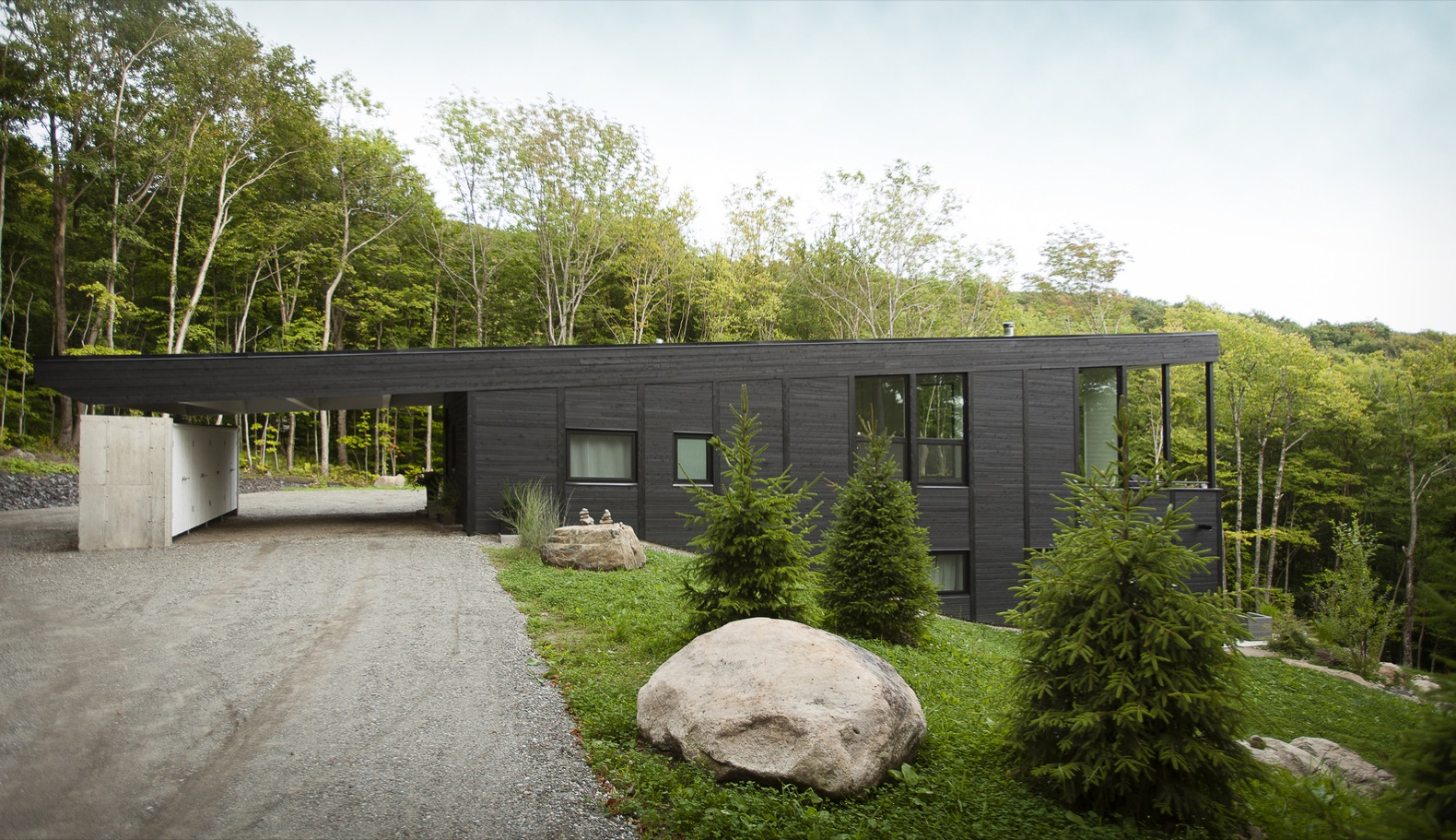 A green-roofed ski cabin blends into the lush Canadian landscape