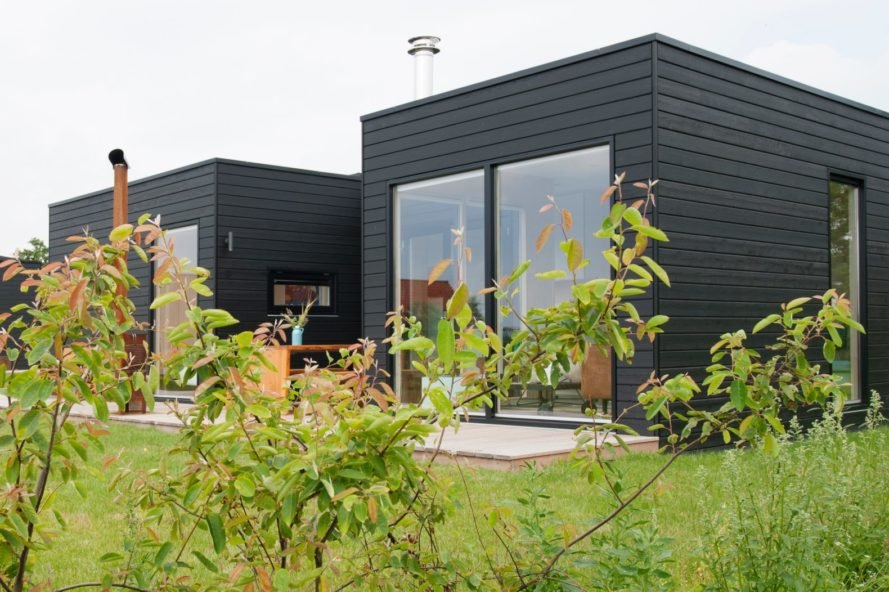 black cabin surrounded by greenery