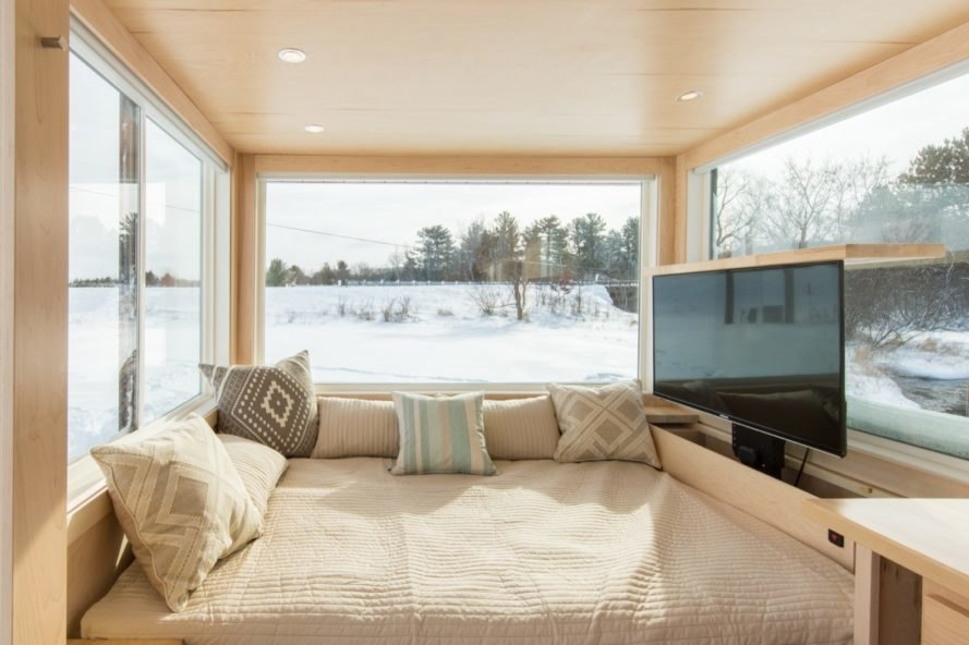 Living space with light bedding on a converted couch bed, large flat screen television, and three large glass windows with views of a snowy landscape