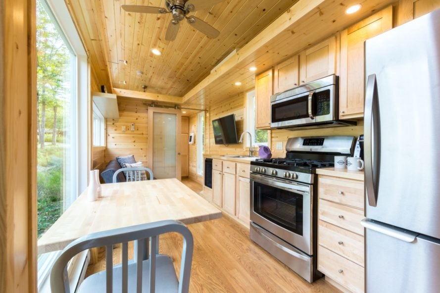 Compact kitchen with stainless steel appliances and light timber cabinets