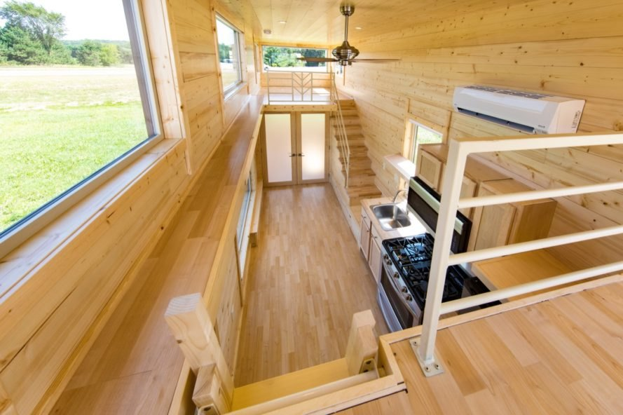 Aerial view of tiny home lined in light timber with several large windows