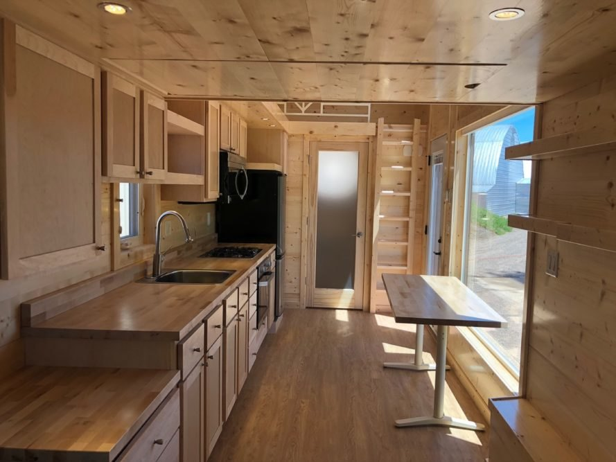 light timber walls, floors and kitchen cabinetry in a compact tiny home