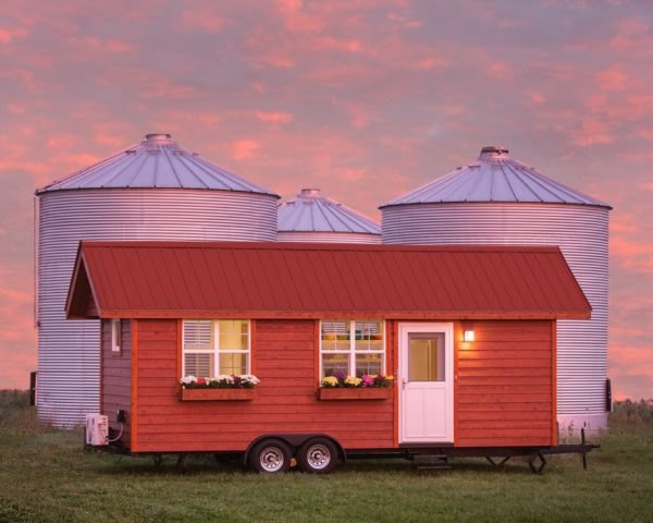 Red tiny home with gabled room in front of silos at dusk