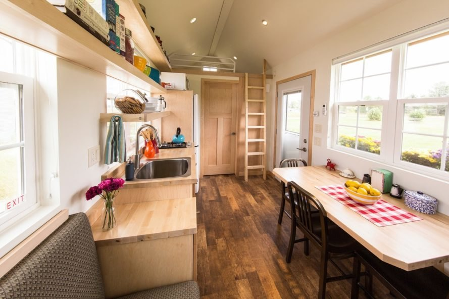tiny home with long, narrow dining table and light timber kitchen cabinets