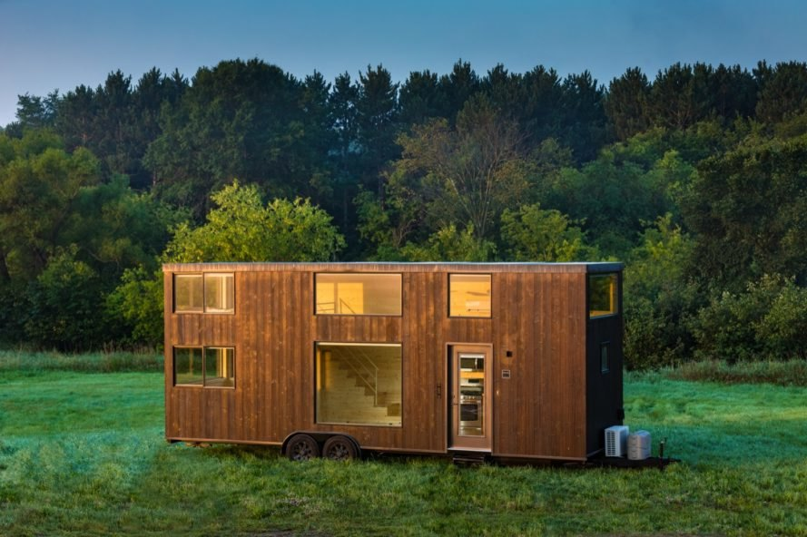 Dark wood tiny home in front of a forest