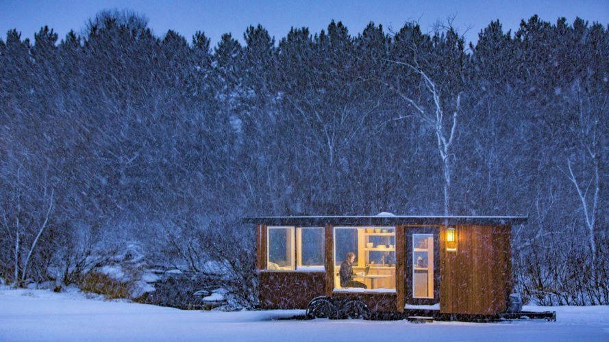 Person on a laptop inside a tiny home seen through a large window of dark wood tiny home on a snowy landscape at night
