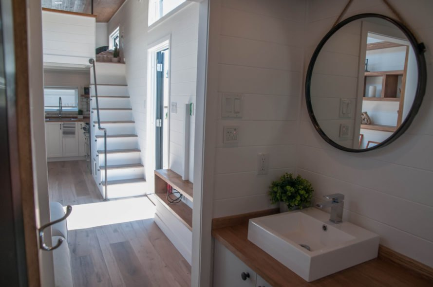 living space with small bathroom and round mirror