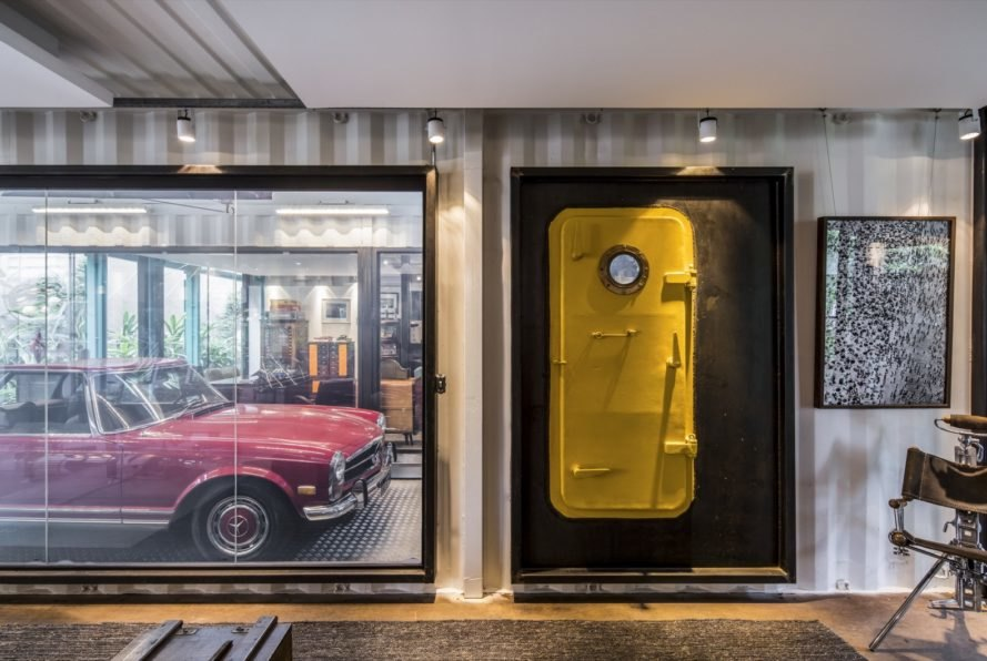 shipping container with yellow door and glass wall revealing a red vintage car