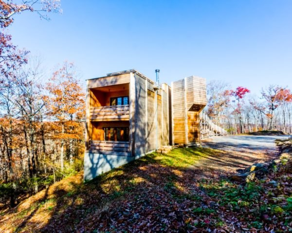 timber clad home on a hill in the forest in autumn
