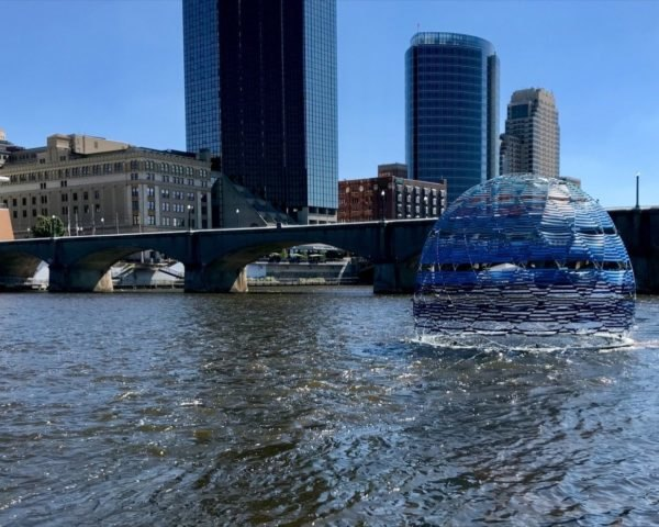 blue dome floating on a river with skyscrapers in background