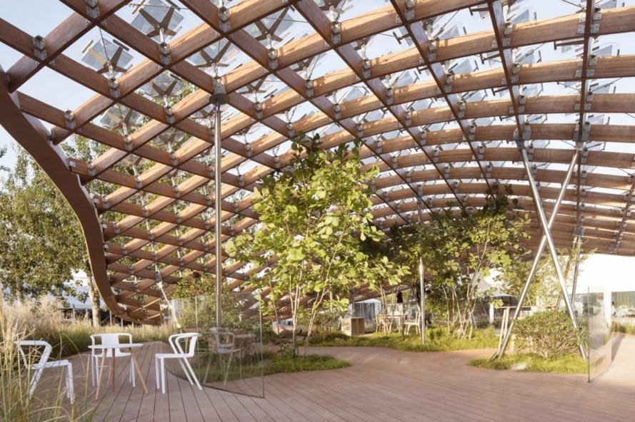 curved wood and glass roof above pavilion with plenty of greenery and seating
