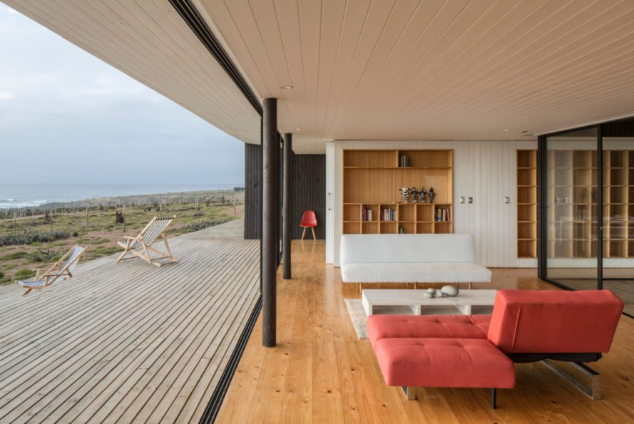 an interior and exterior living space with a red sofa