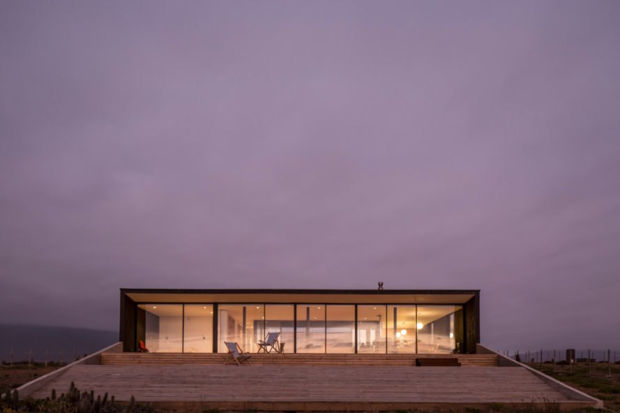 evening view of horizontal home with glass facade