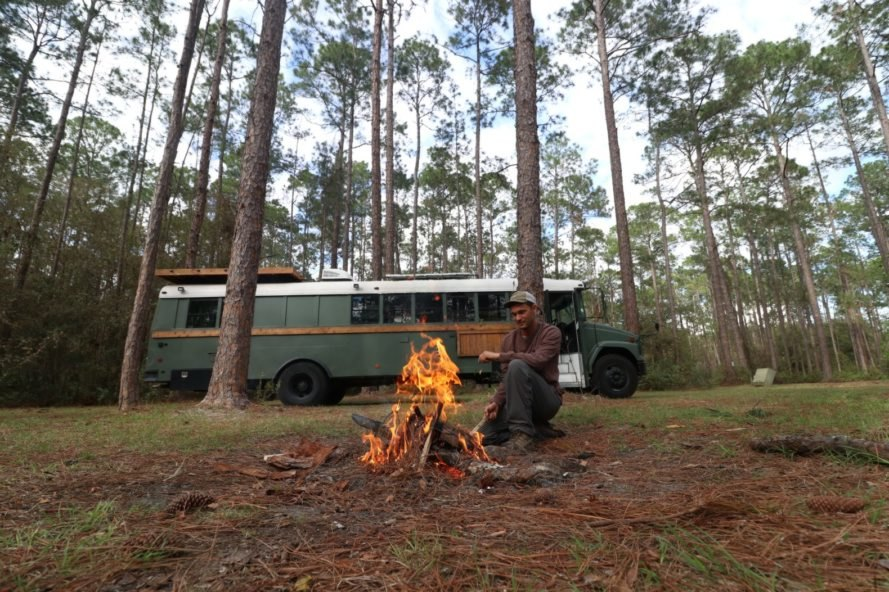 man at fire pit in front of dark green school bus