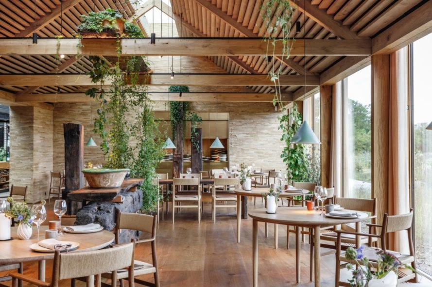 restaurant with wood tables and chairs, glass walls and plenty of hanging plants