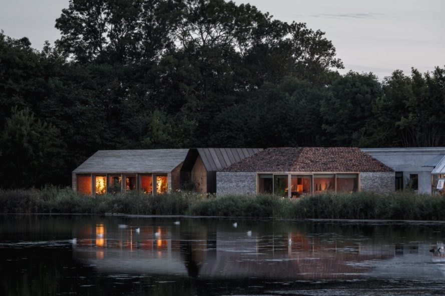 gabled structures clad in timber and brick at dusk with a lake in the foreground