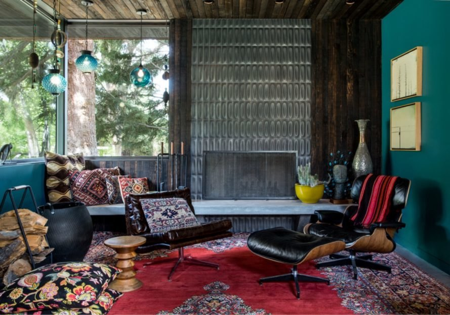 teal painted room with dark leather chairs and colorful patterned rug