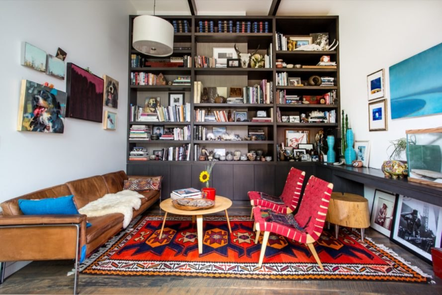 floor-to-ceiling dark wood bookshelf filled with books and small knickknacks and a tan leather couch and red chairs on a colorful patterned rug