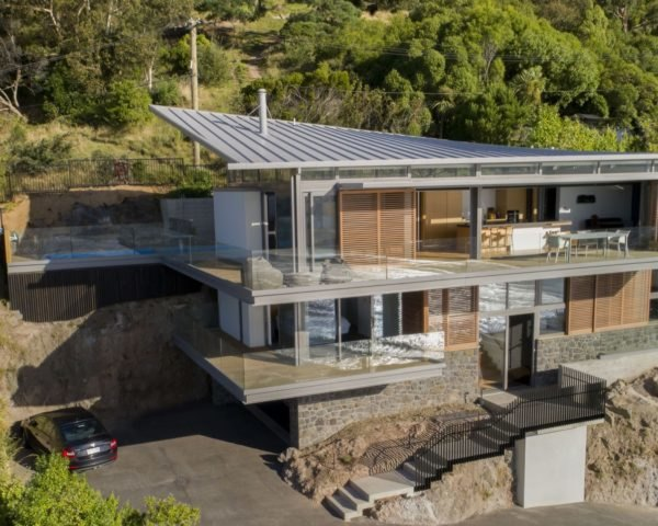 stone home with sloped roof built into green hillside