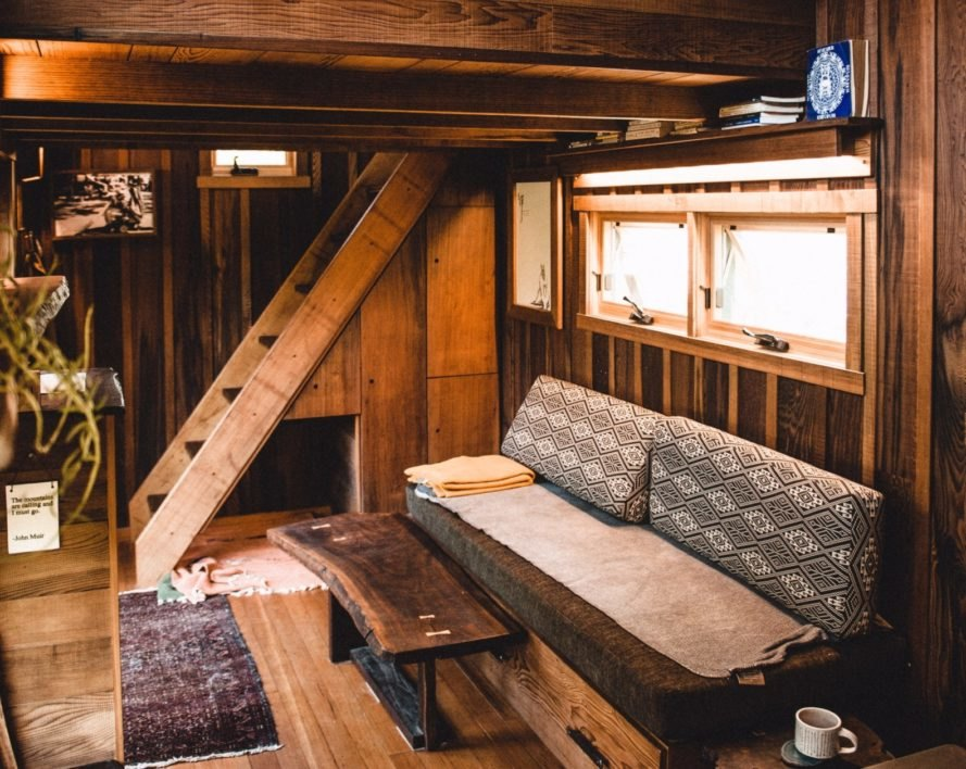 living space in wooden cabin with sofa and a ladder