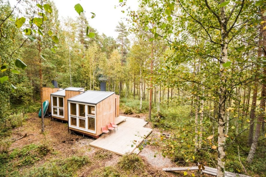 aerial shot of wooden cabin surrounded by forest