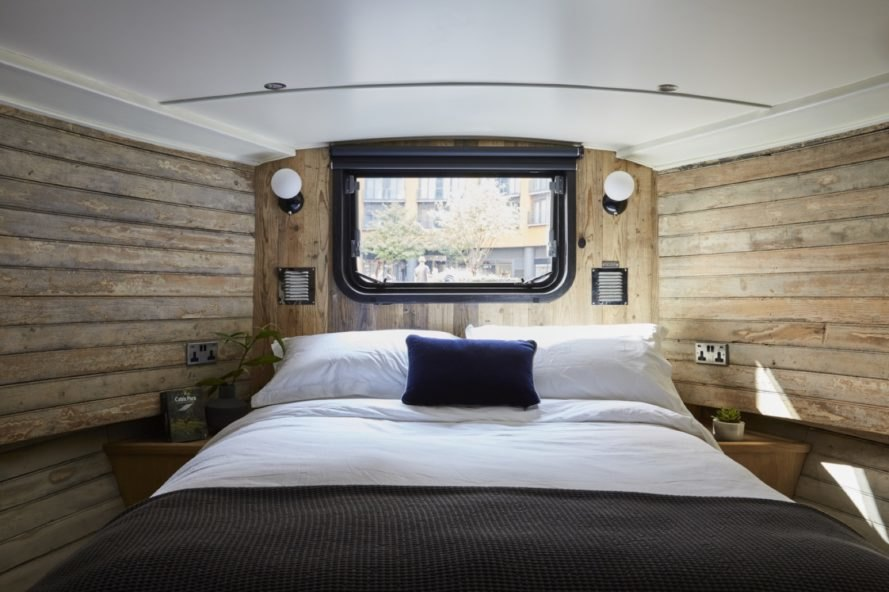 Bed with gray and white blankets and blue throw pillow under a small boat window in a wood-lined room