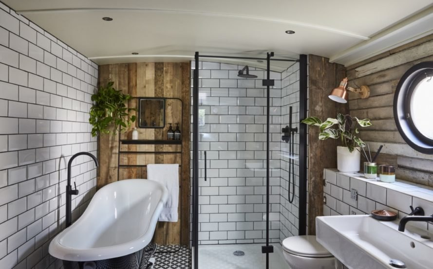 bathroom with white subway tiles, wood accent walls, standalone bathtub, glass shower, and potted and hanging plants