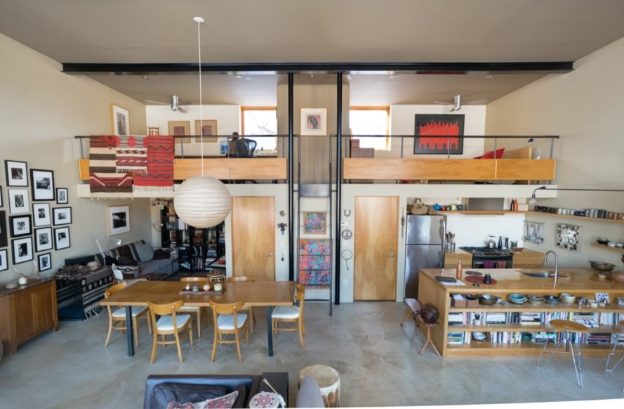 open-plan living area with light wood dining table and kitchen island below lofted bedroom