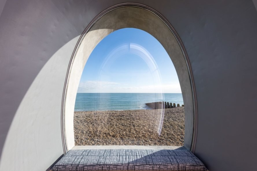 view of a beach through a large curved window