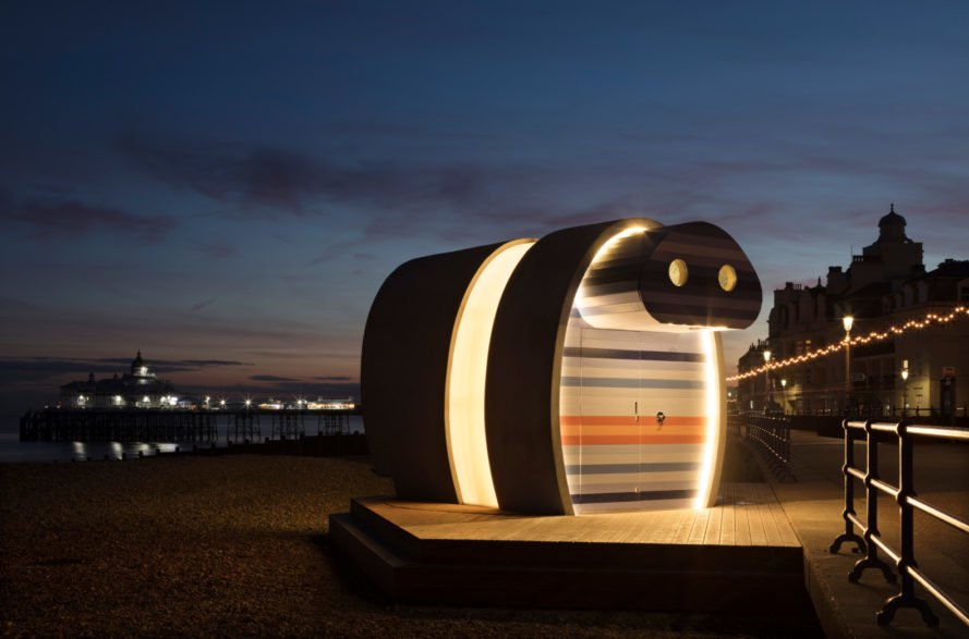 concrete, binocular-shaped beach hut lit from within at night