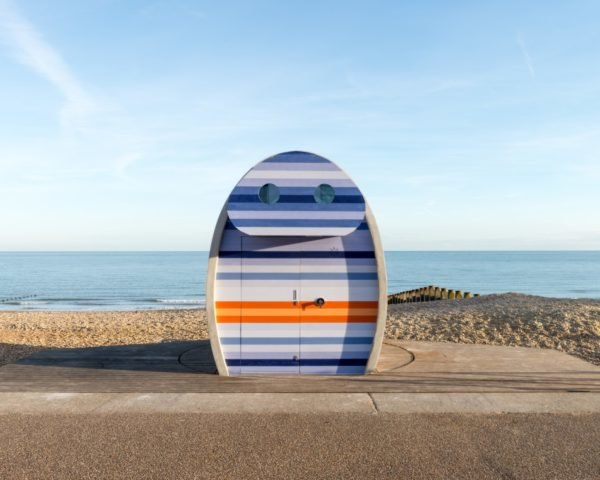 binocular-shaped beach hut with orange and blue front facade