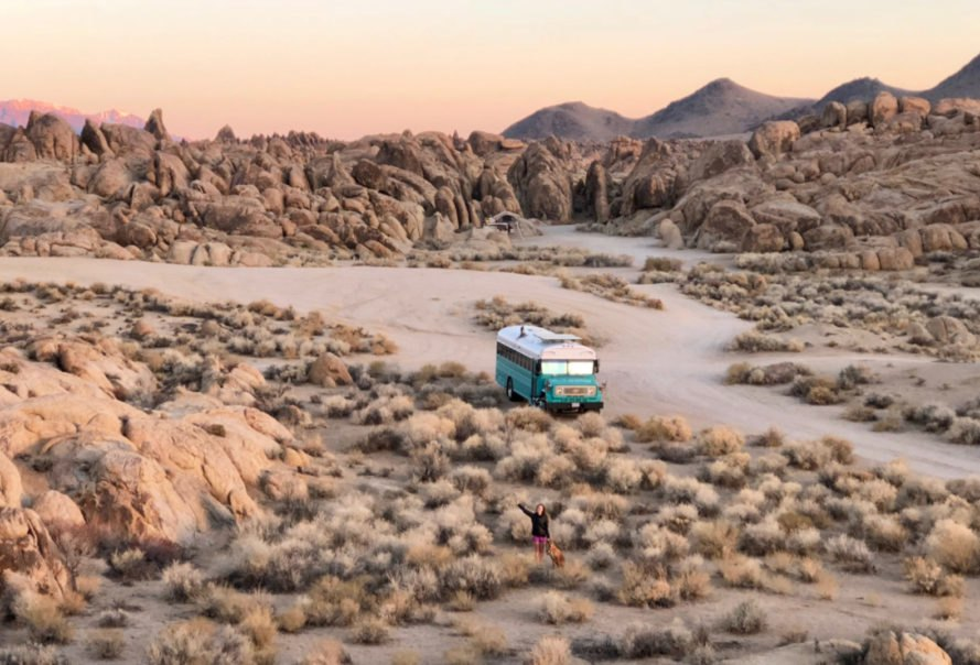 teal bus in the middle of desolate landscape