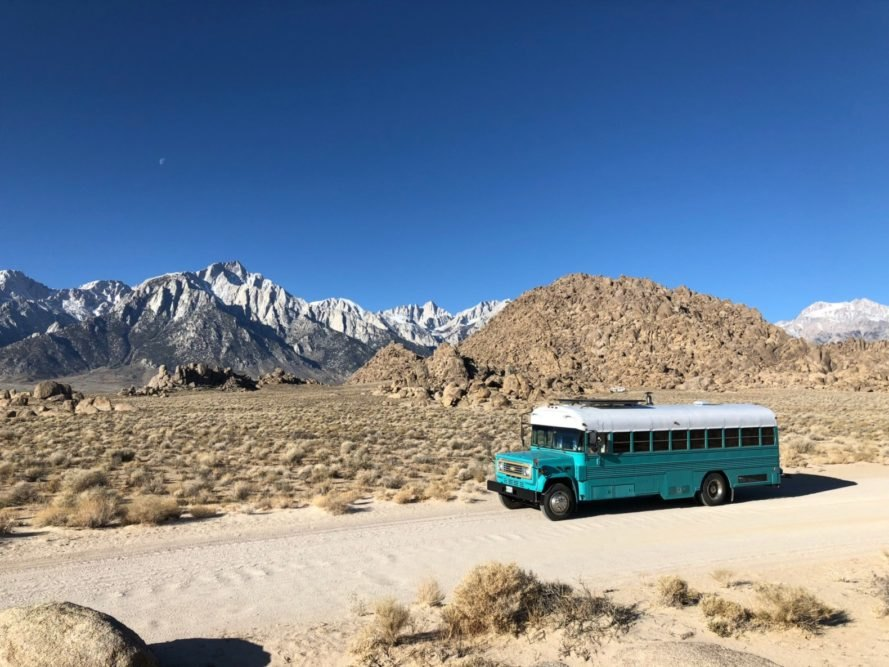 teal bus in front of mountainous landscape