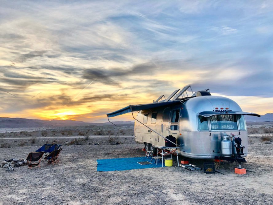 a shiny airstream with overhang over sitting area