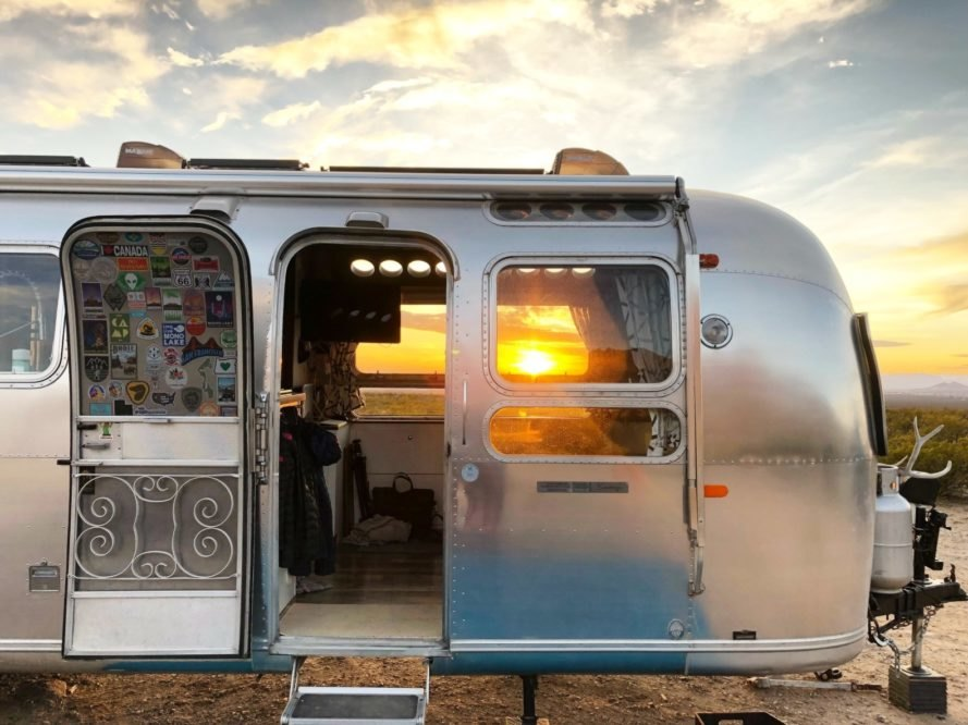 a silver airstream with the sunsetting in the background