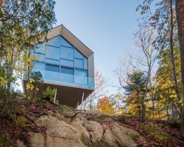 gabled studio building with glass wall on a cliff