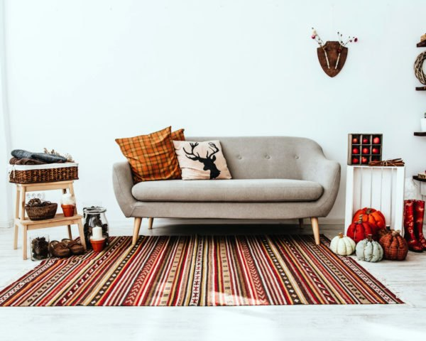 living room with gray couch and orange and red decorations