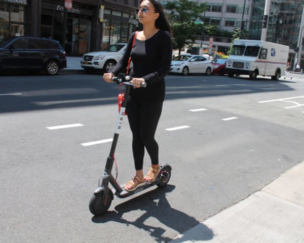 Woman riding a black and white electric scooter on a city street